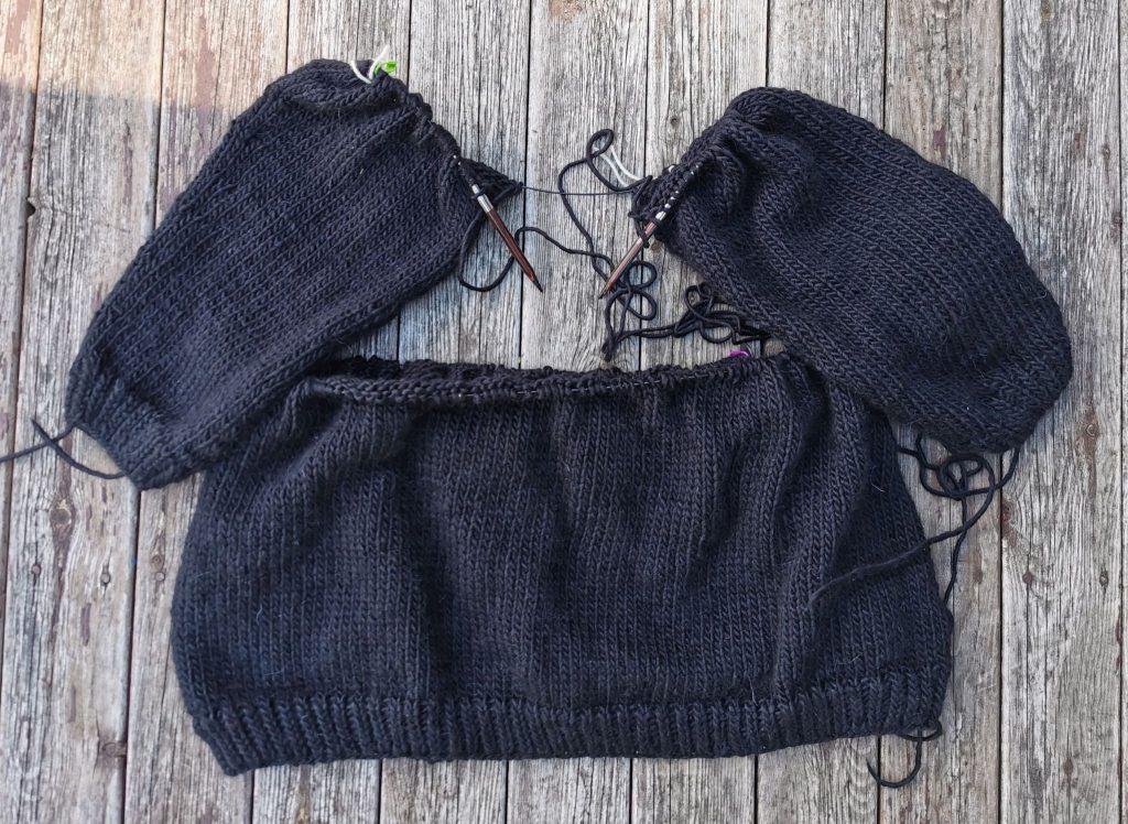 Ermene til genseren hektet på en strikkepinne og starten på bolen til genseren som ligger på et planke-gulv, honeysuckle genser fra Camilla Pihl