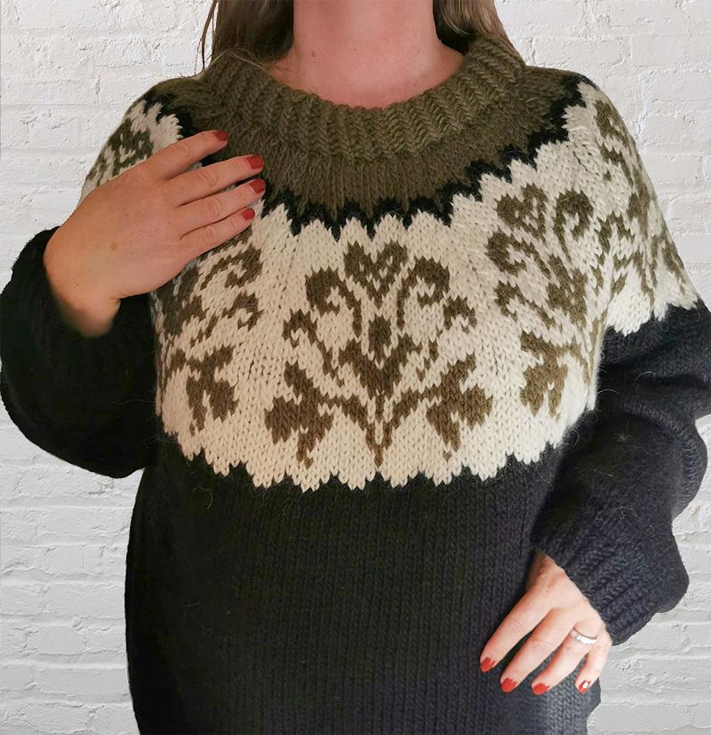 Herdis i kledd Honeysuckle-genser fra Camilla Pihl foran en hvit murvegg