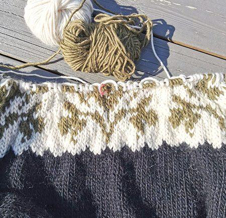 Honeysuckle genser som strikkes med garnnøster som ligger på bordet sammen med strikkepinnene, honeysuckle genser fra Camilla Pihl