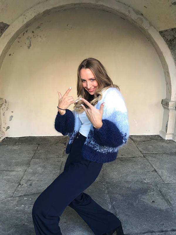Solveig står og smiler bredt mens hun lager ganster-tegn med hendene sine ikledd crocus-genseren under en murbue, crocus-genser fra Camilla Pihl