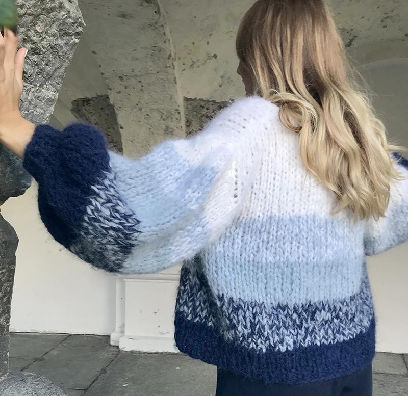 Solveig som står ikledd en hvit og blå cardigan kalt Crocus fra Camilla Pihl mens hun lener seg til en søyle av mur, Crocus camilla pihl