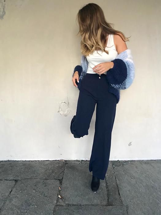 Solveig står og lener seg inntil en vegg med en fot ikledd Camilla Pihl-genseren