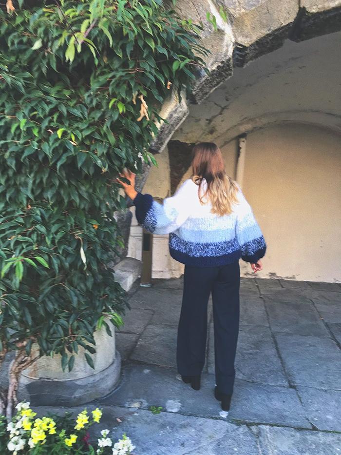 Solveig står ikledd den blåe og hvite Crocus-cardiganen og lener seg inntil en murbue som har vekster som vokser oppover seg