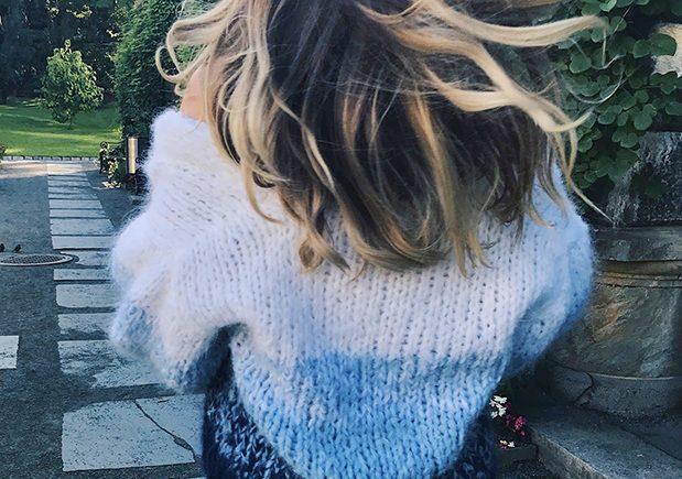 Solveig er ikledd Crocus-genseren med håret flagrende bak seg i vinden med en murvegg med klatreplanter i en park i Bergen, camilla pihl, crocus-genser